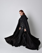 Fantasy Portrait Of A Woman With Red Hair Wearing Dark Leather Assassin Costume With Long Black Cloak. Full Length Standing Pose In Side Profile Isolated Against A Studio Background.