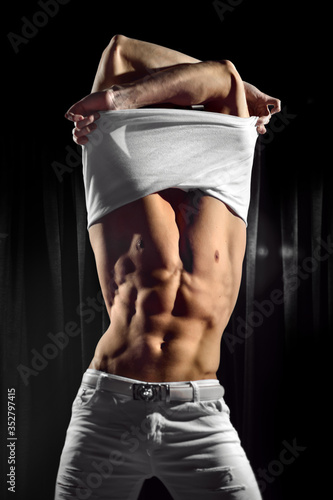 A man with a raised torso takes off his t-shirt. Sexy stripper in a club.