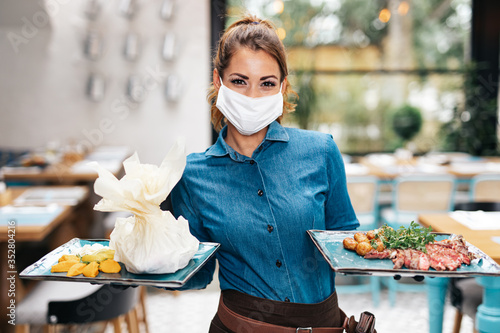 Fototapeta Beautiful young waitress with face protective mask working in exclusive restaurant. Coronavirus or Covid-19 concept. obraz