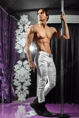 Foto A young handsome man with a muscular naked torso is in a nightclub