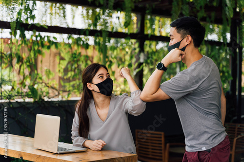Obraz Asian woman and man friends wearing face mask outdoors. Friends greeting and shaking with elbows as new normal. Corona Virus - Covid 19 elbow bumps greeting style to prevent contact and virus spread. - fototapety do salonu