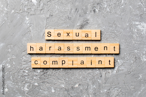 Fototapeta Sexual harassment complaint word written on wood block. Sexual harassment complaint text on table, concept obraz