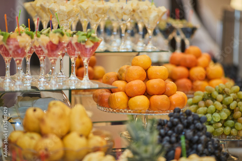 various fruits and fruit desserts on a buffet table in a restaurant