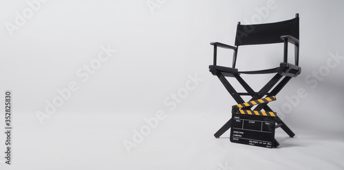 Fotografiet Director chair with black and yellow clapper board or movie slate on white background