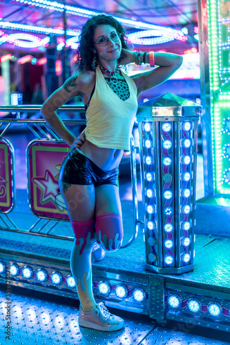 Fotografia a young woman in eighties clothes with curly hair posing in different attraction