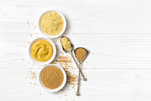 Set Of Yellow Mustard Sauce, Powder And Seeds In Small Bowls With Silver Spoons