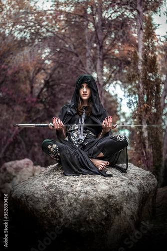 Woman in the forest dressed in a tunic as a sorceress holding a large sword Canvas Print