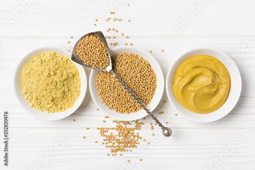 Stampa su Tela Set of yellow mustard sauce, powder and seeds in small bowls with silver spoon