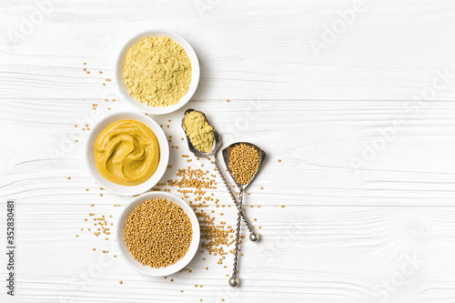 Tablou Canvas Set of yellow mustard sauce, powder and seeds in small bowls with silver spoons