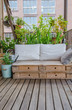 Wooden pallet couch on balcony with plants in background