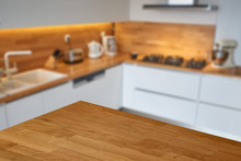 Empty Wooden Table Top Or Countertop Corner With Blurred Modern Kitchen Background.