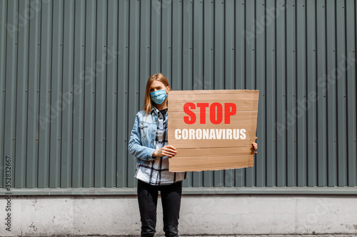 Photo woman in a medical protective mask holds a cardboard placard reading Stop the c
