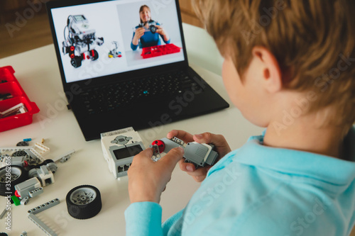 Fotografija kid building robot with online robotic technology lesson