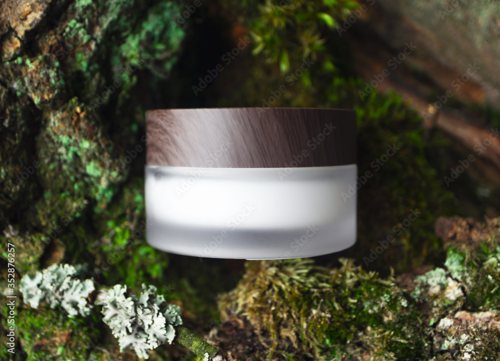 Fototapeta Natural cosmetic face or eye cream skincare blank jar packaging with wooden cup on forest background. Concept eco bio organic beauty product, top view. Tree bark and mosses on backdrop