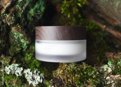 Fototapeta Natural cosmetic face or eye cream skincare blank jar packaging with wooden cup on forest background. Concept eco bio organic beauty product, top view. Tree bark and mosses on backdrop obraz