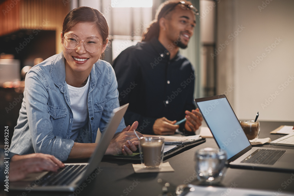 Fototapeta Diverse businesspeople smiling while working with colleagues in