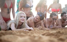 Group Of Cheerful Friends Lying On The Beach Surrounded By The Sea Under The Sunlight At Daytime