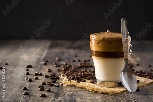 Fototapeta Creamy iced dalgona coffee on wooden table. Copy space obraz