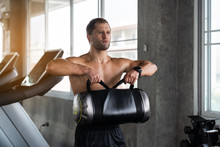 Muscular Young Man Exercising With A Heavy Sandbag In A Fitness Gym. Sporty Man Working Out With Heavy Sandbag