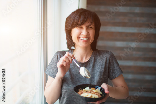 Fototapeta Adult fit slim woman having breakfast alone. Holding bowl in hand and cheerful smiling. Senior well-built person take care about her health. obraz