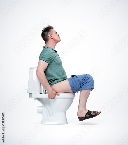 Valokuvatapetti Man in shorts and T-shirt is very tense sitting on the toilet
