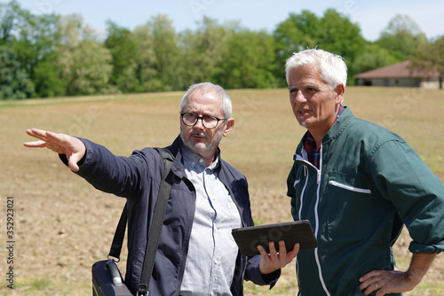Farmer meeting with financial counseller in farm Canvas Print