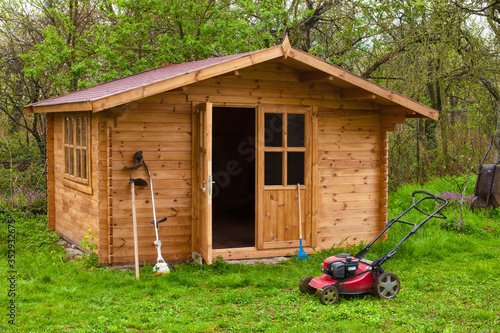 Cuadros en Lienzo Garden shed with hoe, string trimmer,  rake and grass-cutter