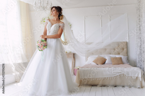 Stampa su Tela A gorgeous young bride in a white wedding dress in the room