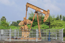 Old Isolated Rusty Oil Pump Jack Extracting Crude Oil And Natural Gas From Well In Green And Cloudy Oil Fields Of India, Asia