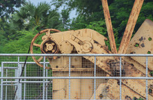 Close-up Of Old Rusty Pump Jack Machinery Extracting Crude Oil And Natural Gas From Well In Green Oil Field