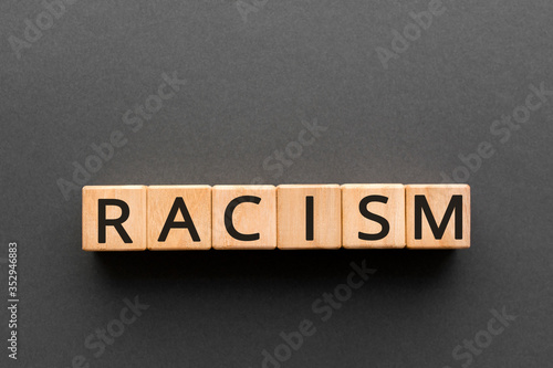 Photo Racism - word from wooden blocks with letters, the belief of inequality of human