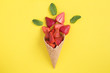canvas print picture - Ice cream cone with chopped strawberry on  the yellow  background. Location vertical. Top view.