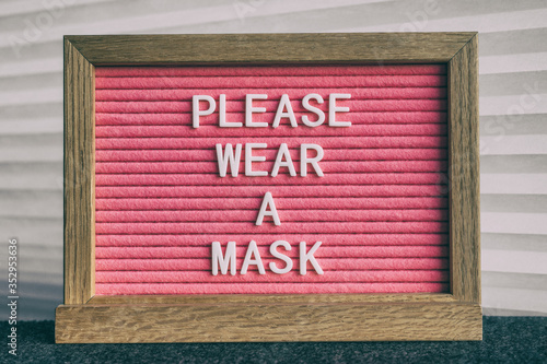 Obraz COVID-19 sign PLEASE WEAR A MASK at grocery store entrance for coronavirus prevention. Message on pink felt letter board. Compulsory measure in businesses for face protection wearing. - fototapety do salonu