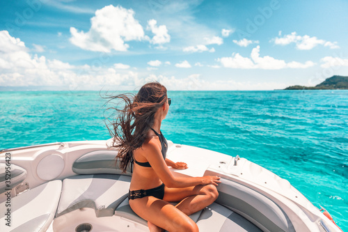 Fototapeta Luxury yacht woman enjoying freedom on deck in the wind relaxing on high end boat summer vacation trip upscale lifestyle of young rich people. Elegant black bikini, long hair and sun tanned body. obraz