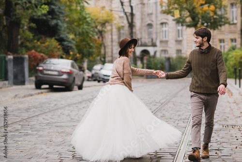 Romantic and happy caucasian couple in casual wedding clothes walking and hugging at the city streets Wallpaper Mural