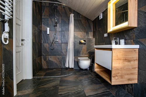 Fotografía Interior of modern stylish bathroom with black tiled walls, curtain shower place and wooden furniture with wash basin and big illuminated mirror