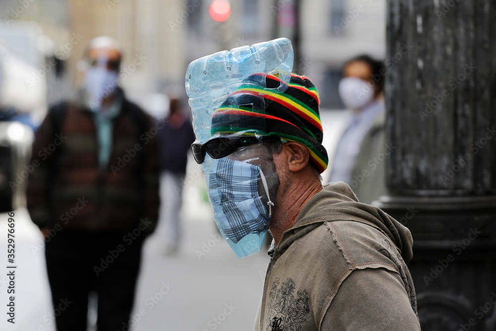 Fototapeta A elderly man wears a piece of plastic water bottle as a face mask to protect from Coronavirus outbreak, COVID-19, in downtown Sao Paulo, Brazil.
