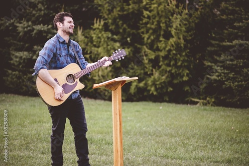 Photo Young male in a park holding a guitar and playing a song from the Christian hymn