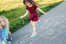 Cute Adorable Children Girls Friends Playing Jumping Hopscotch Outdoors. Funny Activity Game For Kids On Playground Outside. Summer Backyard Street Sport For Children. Happy Childhood Lifestyle.