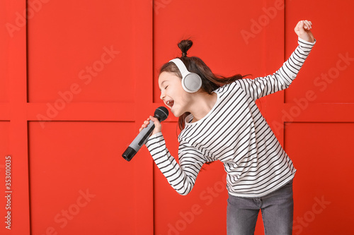 Fotografie, Obraz Cute little girl singing against color background