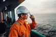 canvas print picture - Filipino deck Officer on deck of vessel or ship , wearing PPE personal protective equipment. He speaks to VHF walkie-talkie radio in hands. Dream work at sea