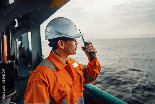 Obraz Filipino deck Officer on deck of vessel or ship , wearing PPE personal protective equipment. He speaks to VHF walkie-talkie radio in hands. Dream work at sea - fototapety do salonu