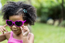 Close Up Shot Of Stylish Or Happy Little Child Girl With Curly Hair In Sunglasses Smiling On Outdoor. Confidence That Can Only Grow Out Of A Strong Heart. African American Kid Model With Copy Space.