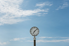 An Analog White Clock With A Sky With A Few Clouds As Background. Pass Of The Time Concept. Horizontal With Copy Space.