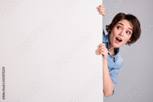 Fototapeta Portrait of astonished girl close cover big white banner see incredible novelty impressed look scream wow omg wear casual style clothes isolated over gray color background obraz