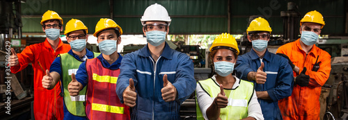 Fotografie, Obraz Group of Worker wearing face shield or disposable face mask work in factory to help prevent and fight Coronavirus(Covid-19) or Air dust pollution together wide banner