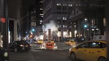 Steam Over City Street. New York City Scene At Night. Traffic Cars Lights. New York City. Cars Driving Through Sewage Steam After Heavy Rain, New York City.