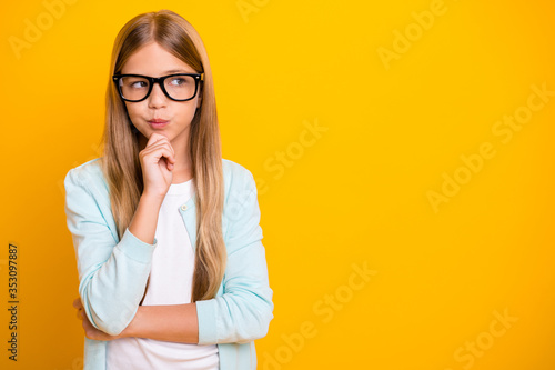 Obraz Photo of beautiful little lady hold arm on chin diligent student pupil school girl look side empty space tricky person wear specs casual shirt isolated yellow bright color background - fototapety do salonu