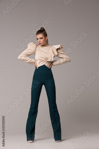 Woman model in fashionable clothes. Stylish look. The girl poses in the studio in long flared trousers and a blouse with wide and magnificent sleeves.