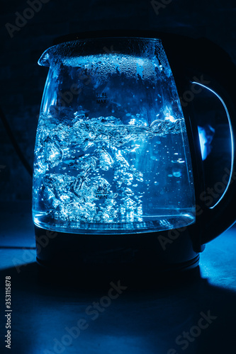 Fotografering Boiling glass black teapot with blue backlight on a black background